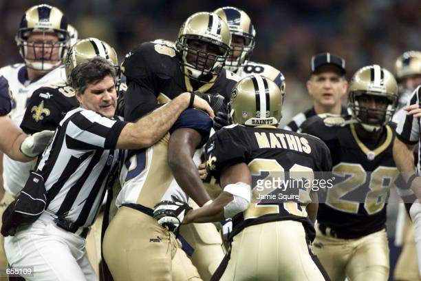 Umpire Carl Paganelli breaks up a fight between Marshall Faulk of the St Louis Rams and Kevin Mathis of the New Orleans Saints during Sunday's final...