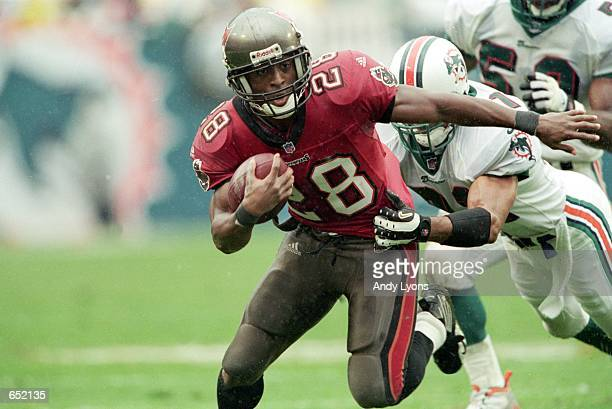 Warrick Dunn of the Tampa Bay Buccaneers runs with the ball against Brock Marion of the Miami Dolphins during the game at the Pro Players Stadium in...