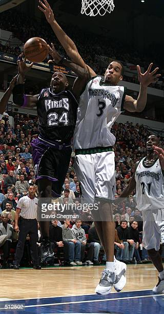 Bobby Jackson of the Sacramento Kings gets fouled on his way to the basket by Loren Woods of the Minnesota Timberwolves at Target Center in...