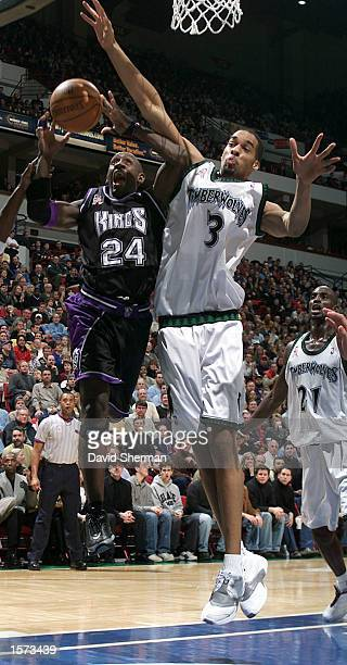 Bobby Jackson of the Sacramento Kings is fouled on his way to the basket by Loren Woods of the Minnesota Timberwolves at Target Center in Minneapolis...