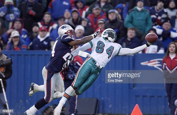 Chris Chambers of the Miami Dolphins dives to catch a pass under pressure from Ty Law of the New England Patriots during the game at Foxboro Stadium...