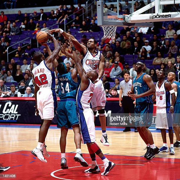 Elton Brand Michael Olowokandi and Lamar Odom of the Los Angeles Clippers combine for a block attempt on Lee Nailon of the Charlotte Hornets during a...