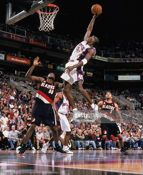 Forward Bo Outlaw of the Phoenix Suns dunks the ball as forward Zachary Randolph of the Portland Trail Blazers stands under the basket during the NBA...