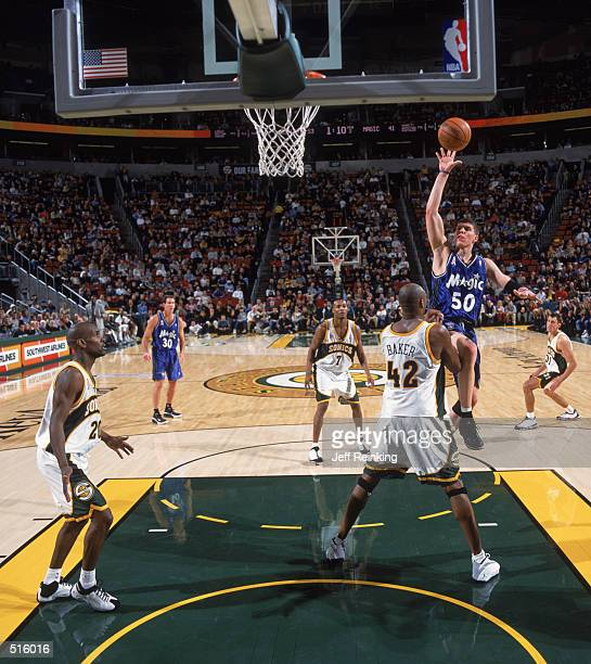 Forward Mike Miller of the Orlando Magic shoots over forward Vin Baker of the Seattle SuperSonics during the NBA game at Key Arena in Seattle...