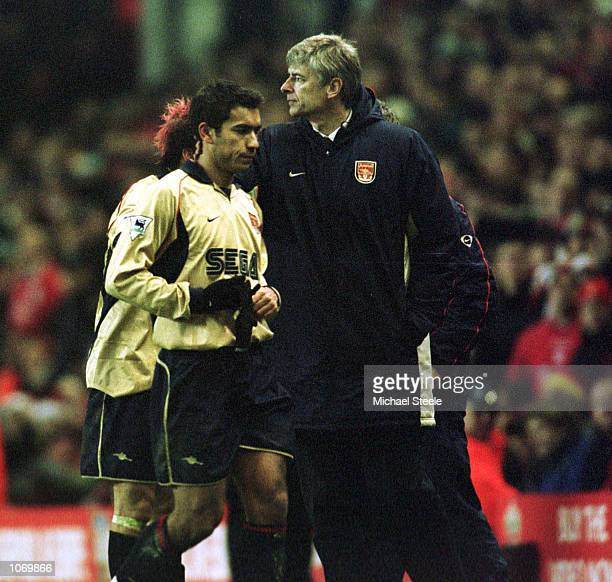 Giovanni Van Bronckhorst of Arsenal leaves the field with manager Arsene Wenger after being sent off during the match between Liverpool and Arsenal...