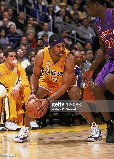 Guard Derek Fisher of the Los Angeles Lakers holds the ball as guard Alvin Williams of the Toronto Raptors plays defense during the NBA game at the...