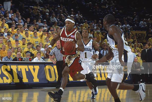 Guard Ryan Sidney of the Boston College Eagles dribbles the ball up court while guard Avery Queen of the Michigan Wolverines tries to get back in the...
