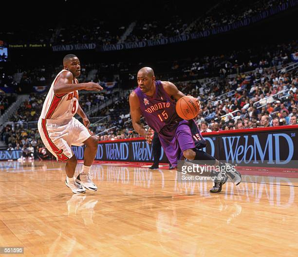 Guard Vince Carter of the Toronto Raptors dribbles the ball past guard Emanual Davis of the Atlanta Hawks protects the basket during the NBA game at...