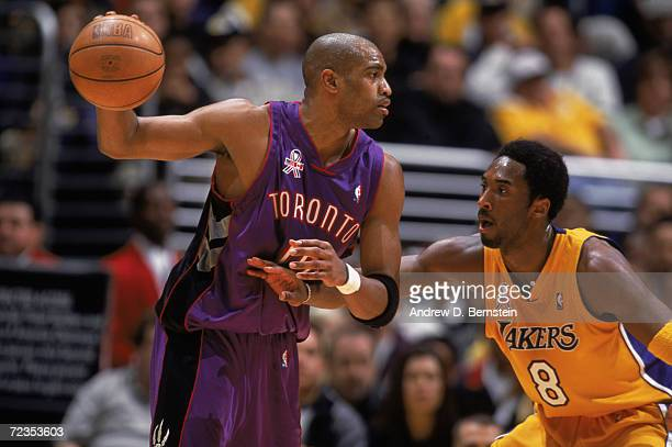 Guard Vince Carter of the Toronto Raptors holds the ball as guard Kobe Bryant of the Los Angeles Lakers plays defense during the NBA game at the...