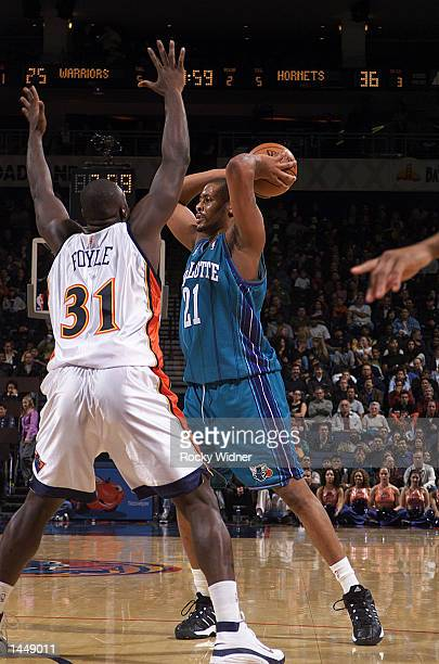 Jamaal Magliore of the Charlotte Hornets looks for the open man as Adonal Foyle of the Golden State Warriors defends him at The Arena in Oakland...