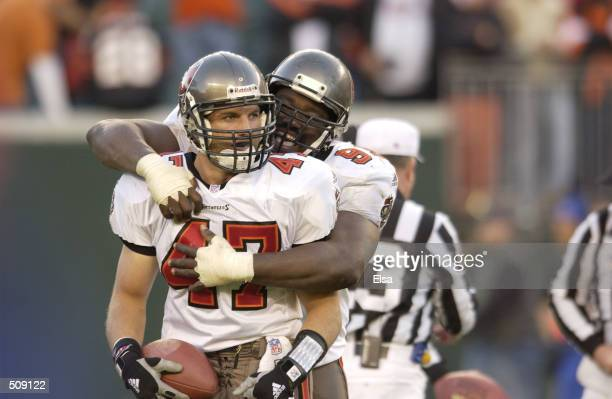 John Lynch of the Tampa Bay Buccaneers is congratulated by teammate Warren Sapp after recovering a fumble which set up the winning field goal against...