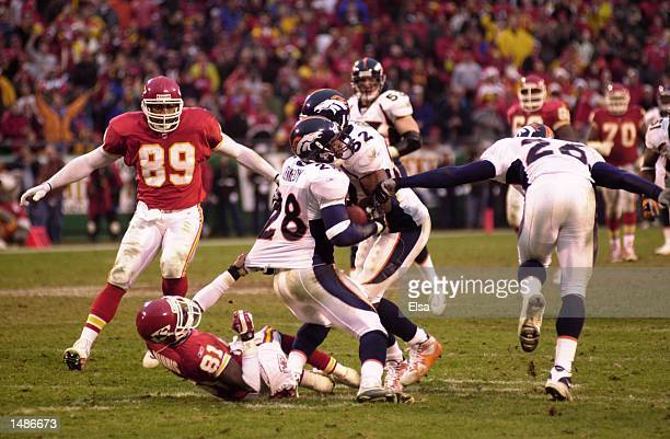 Kenoy Kennedy of the Denver Broncos is pulled down by Marvin Minnis of the kansas City Chiefs during the game at Arrowhead Stadium in Kansas City...