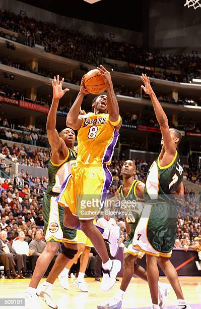 Kobe Bryant of the Los Angeles Lakers blows past Rashard Lewis and Vin Baker of the Seattle SuperSonics during the first half at Staples Center in...