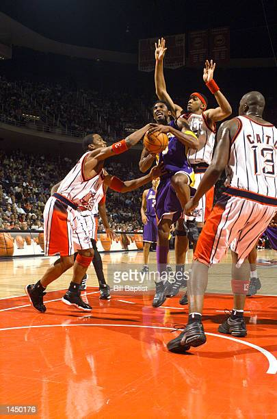 Kobe Bryant of the Los Angeles Lakers is fouled by Cuttino Mobley of the Houston Rockets as Eddie Griffin and Kelvin Cato of the Houston Rockets help...