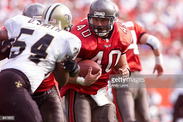 Mike Alstott of the Tampa Bay Buccaneeers tries to get by Darrin Smith of the New Orleans Saints during the game at Raymond James Stadium in Tampa...