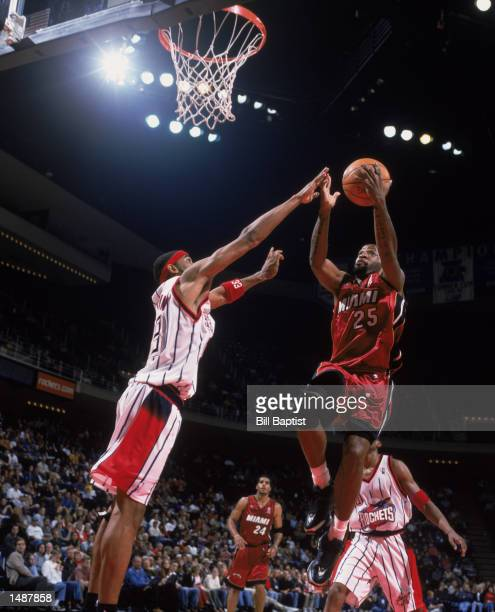Point guard Anthony Carter of the Miami Heat shoots over forward Eddie Griffin of the Houston Rockets during the NBA game at the Compaq Center in...