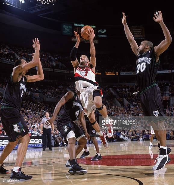 Point guard Damon Stoudamire of the Portland Trail Blazers shoots over center Loren Woods of the Minnesota Timberwolves during the NBA game at the...
