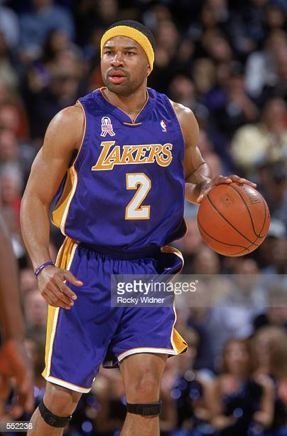 Point guard Derek Fisher of the Los Angeles Lakers dribbles the ball during the NBA game against the Golden State Warriors at the Arena in Oakland in...