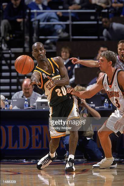 Point guard Gary Payton of the Seattle SuperSonics passes the ball as guard Bob Sura of the Golden State Warriors plays defense during the NBA game...