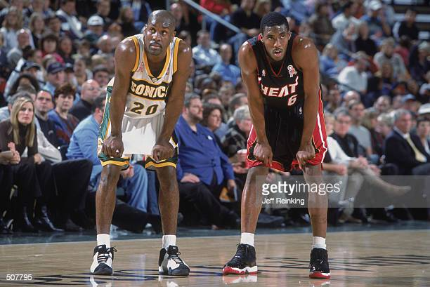 Point guard Gary Payton of the Seattle SuperSonics rests with guard Eddie Jones of the Miami Heat during the NBA game at Key Arena in Seattle...