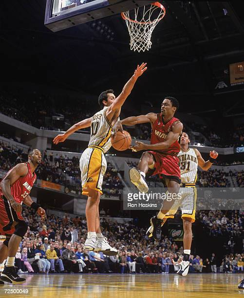 Point guard Rod Strickland of the Miami Heat passes around center Jeff Foster of the Indiana Pacers during the NBA game at Conseco Fieldhouse in...