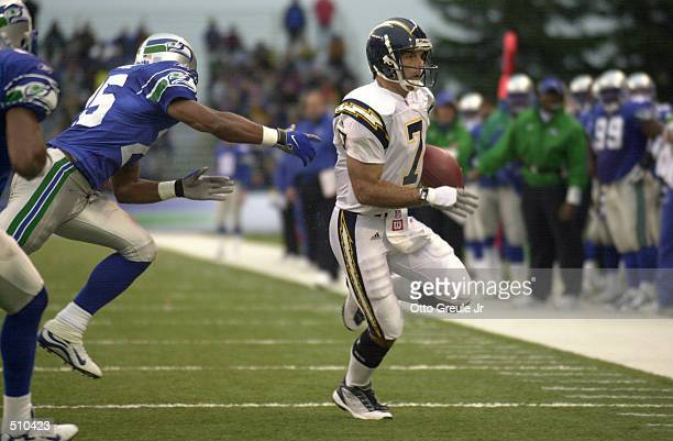 Quarterback Doug Flutie of the San Diego Chargers is under pressure from Reggie Tongue of the Seattle Seahawks during the game at Husky Stadium in...