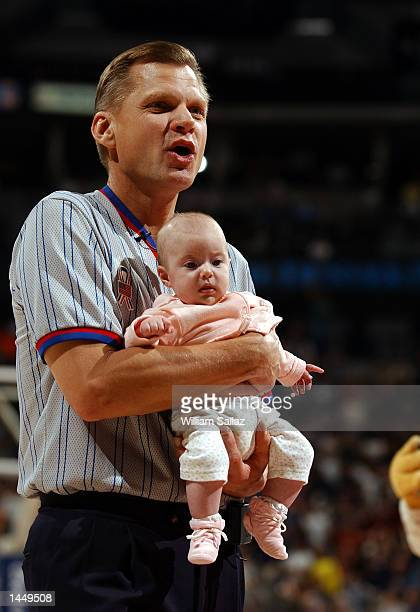 Referee Steve Javie looks for the baby''s mother after Rocky the Nuggets mascot left him with him during a timeout as the Charlotte Hornets take on...