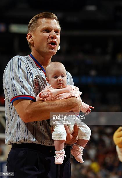 Referee Steve Javie looks for the baby's mother after Rocky the Nuggets mascot left him with him during a timeout as the Charlotte Hornets take on...