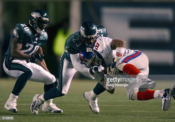 Tiki Barber of the New York Giants is tackled by Troy Vincent of the Philadelpia Eagles as Brian Dawkins backs him up during Week 16 NFL action at...