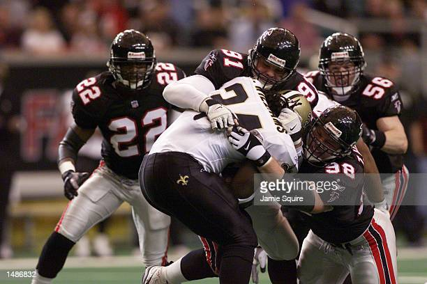 Travis Hall and Brady Smith gang up on Ricky Williams of the New Orleans Saints during the game at the Georgia Dome in Atlanta Georgia The Saints won...