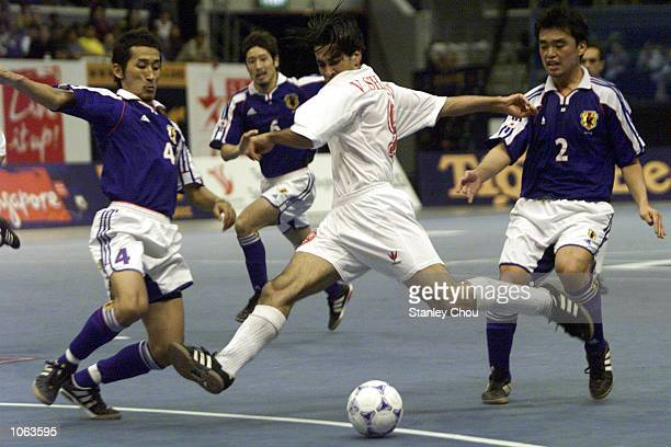 Vahid Shamsaee of Iran unleashes a shot while Ichibara Takaaki and Suzumure Takuya of Japan moves in to intercept during the Plate final between Iran...