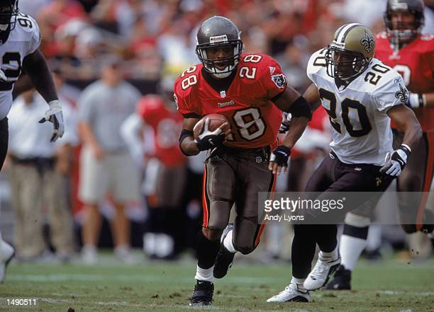 Warrick Dunn of the Tampa Bay Buccaneers carries the ball up the field during the game against the New Orleans Saints at Raymond James Stadium in...