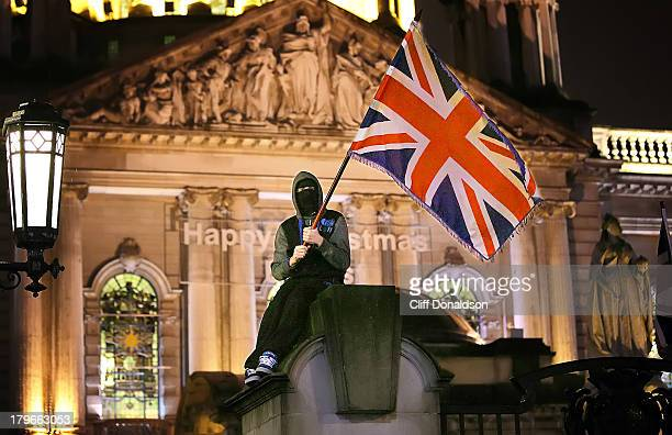 A protester climbs on the gates of Belfast city hall to take part in a protest over restrictions on flying the Union flag at the building Picture...