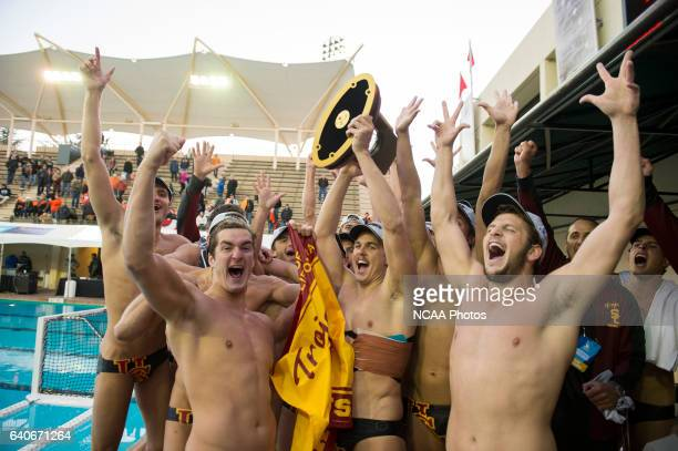 USC players celebrate with the championship trophy after a victory against University of the Pacific during the Division I Men's Water Polo...