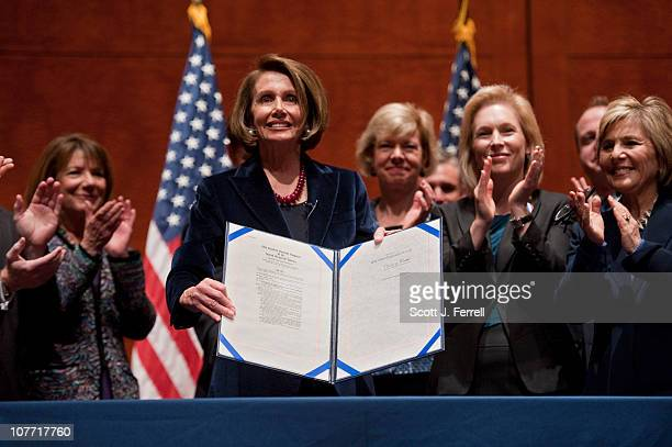 House Speaker Nancy Pelosi DCalif signs the the bill that repeals the militaryÕs ÒdonÕt ask donÕt tellÓ policy Rep Tammy Baldwin DWis Sen Kirsten...