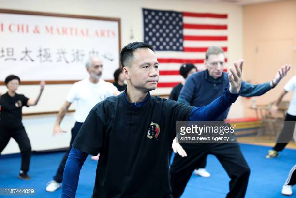 NEW YORK Dec 9 2019 Chen Sitan front practices Tai Chi with students at Sitan Tai Chi and Martial Arts a martial art school in Syosset of New York...