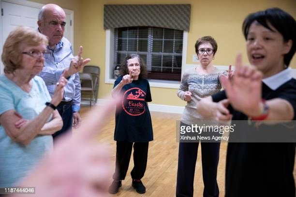 NEW YORK Dec 9 2019 Lin Xu 1st R wife of Chen Sitan teaches senior students during a group Tai Chi class at the club house at The Seasons in East...