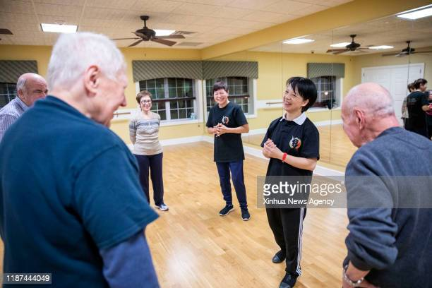 NEW YORK Dec 9 2019 Lin Xu 2nd R wife of Chen Sitan talks with senior students during a group Tai Chi class at the club house at the club house at...