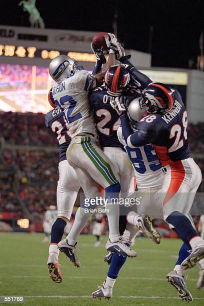 Darrell Jackson of the Seattle Seahawks jumps to catch the football while Delta O''Neal and teammate Kenoy Kennedy of the Denver Broncos try to stop...