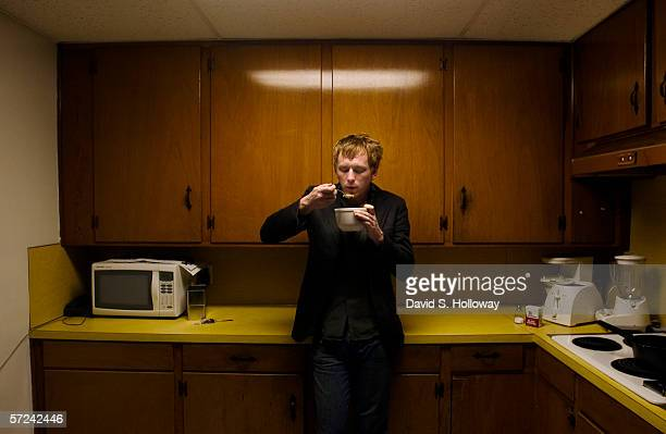 Decahedron bassist Jonathan Ford enjoys a moment alone eating in the kitchen after a late night performance on February 06 2004 in St Augustine...