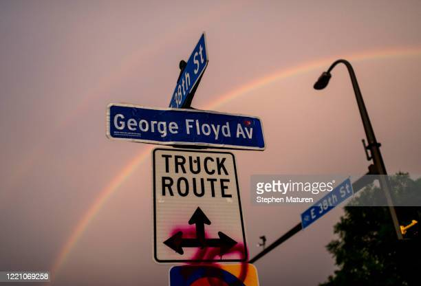 """Decal pasted onto a street sign marks """"George Floyd Avenue"""" as a rainbow sprawls across the sky over a memorial site at 38th St and Chicago Avenue on..."""