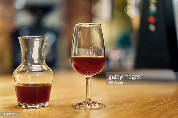 Decanter and wine glass of cold brew coffee on coffee shop counter