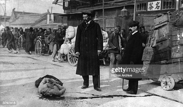 A decapitated body lies in the street while two foreigners look on during the Revolution in China 191112