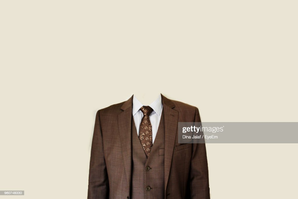 Decapitated Businessman Standing Against Beige Background : Stock Photo