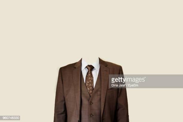 decapitated businessman standing against beige background - decapitado fotografías e imágenes de stock