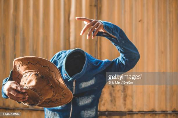 Decapitated Man Holding Hat While Standing Outdoors