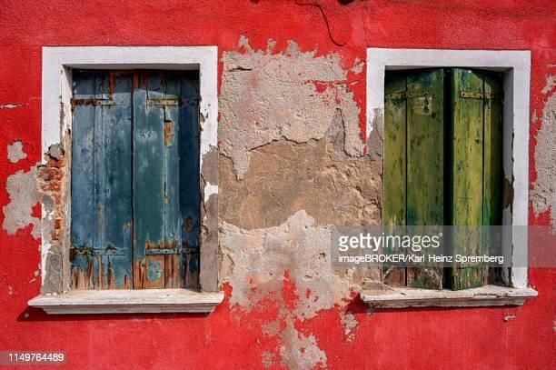 decayed colorful house facade with old shutters, burano, venice, italy - burano foto e immagini stock