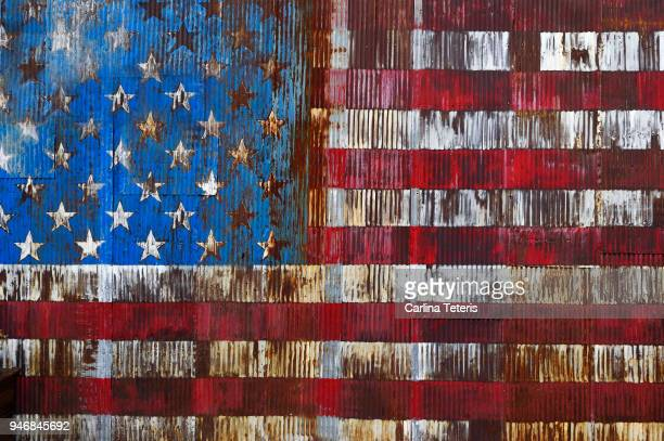 decaying american flag painted on a rusty door - deterioration stock pictures, royalty-free photos & images