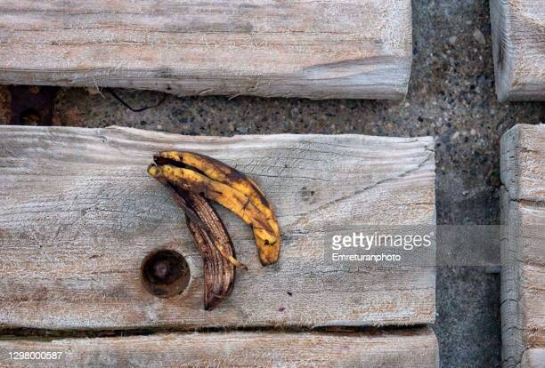 decaying banana peel on a wooden bench. - emreturanphoto stock pictures, royalty-free photos & images