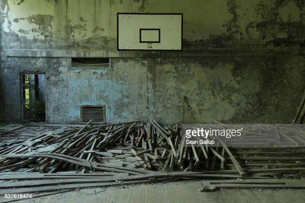 A decaying basketball court stands in the ghost town of Pripyat not far from the Chernobyl nuclear power plant on August 18 2017 in Pripyat Ukraine...
